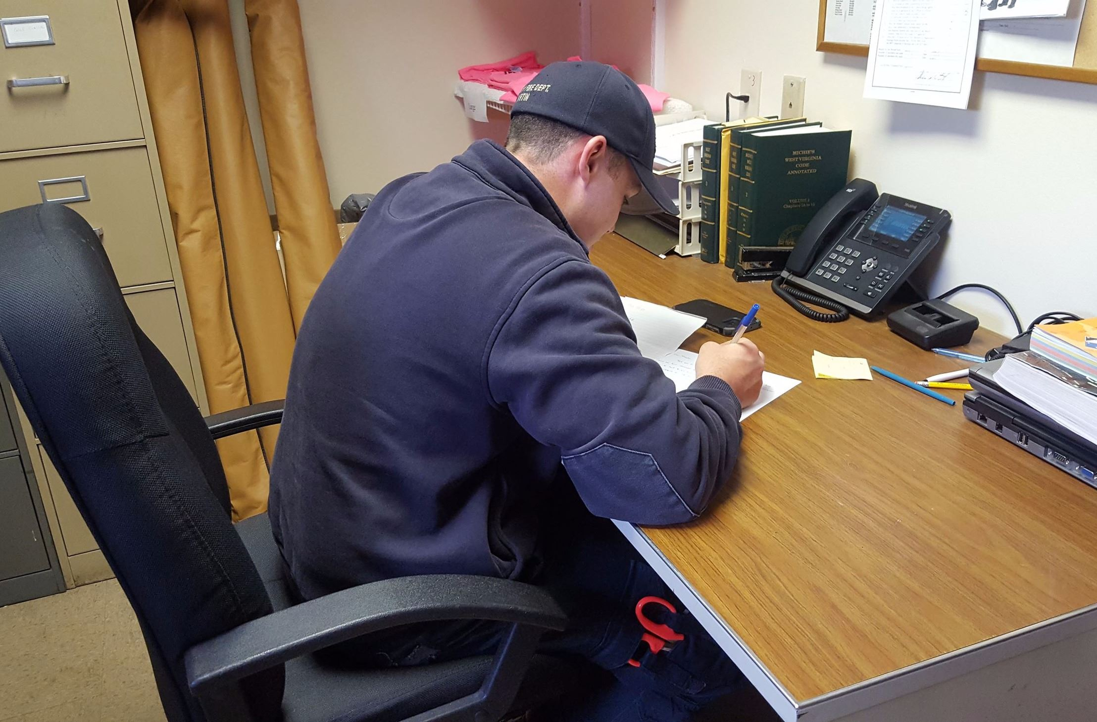 Weirton firefighter Phil Martin works on a letter to the Firefighters Pen Pal Club